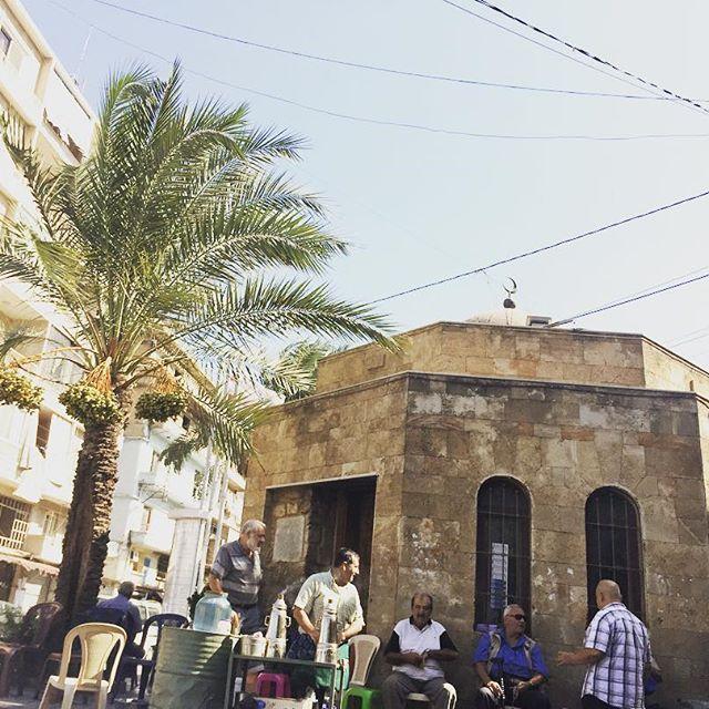 Straßenszene mit Männer vor Gebäude, die Kaffee trinken