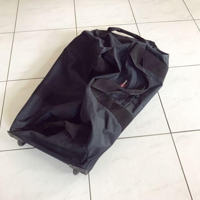 Eine blaue sehr große Reisetasche liegt am Boden