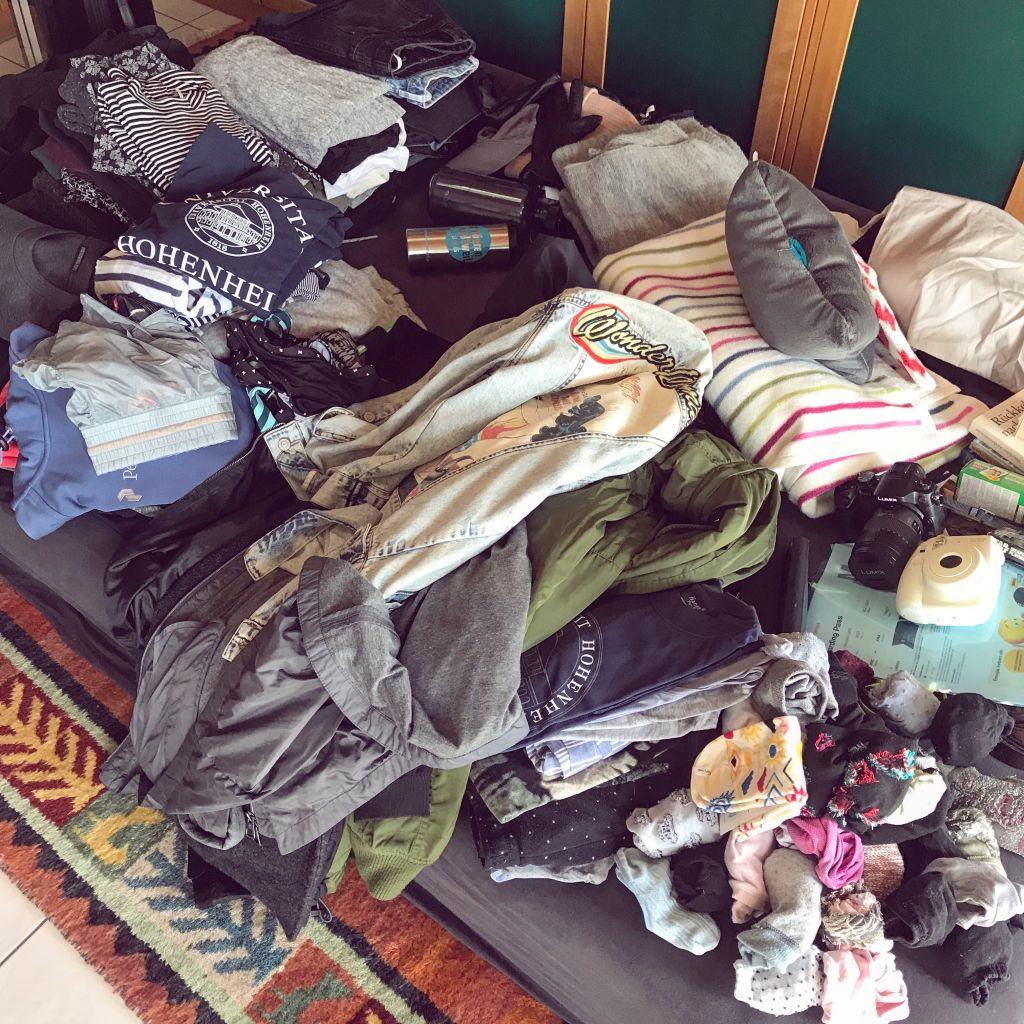 chaotischer Haufen Kleidungsstücke auf Matratze verteilt