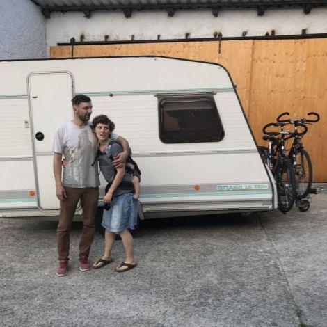 zwei Menschen und Kind vor Wohnwagen