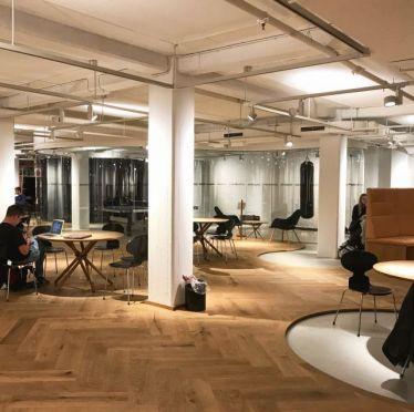 Moderner, heller Raum mit runden Gruppenarbeitstischen und einem Boxsack sowie einer Tischtennisplatte
