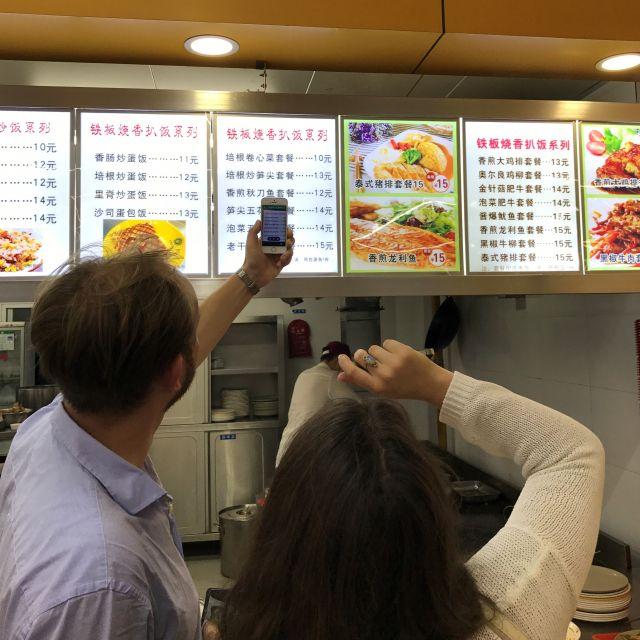 Deutsche Studierende beim essen bestellen mit Hilfe von Smartphone und Google Translater