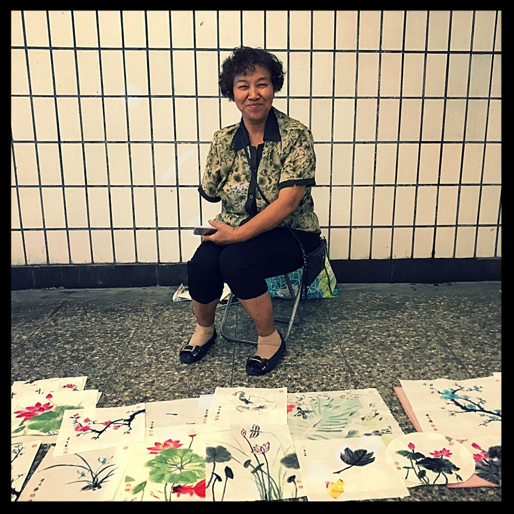Frau Xiang vor ihren Blumenbildern