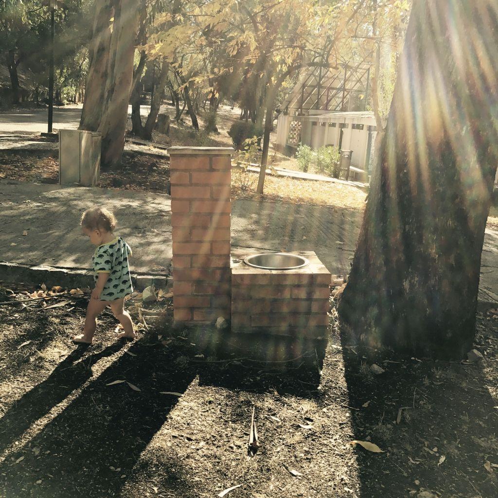 Kind spielt draußen im Gegenlicht
