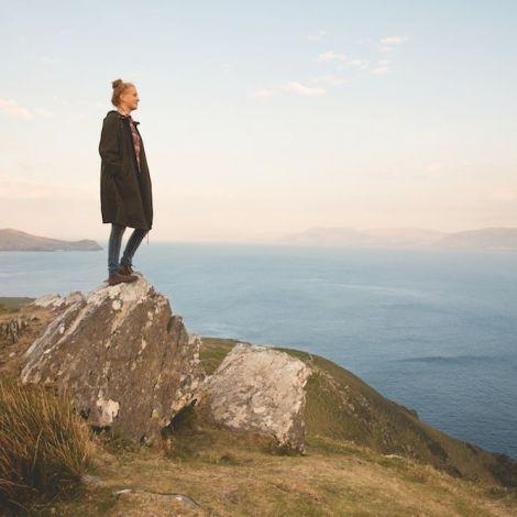 Silva steht auf einem Felsen an der irischen Küste und blickt aufs Meer.