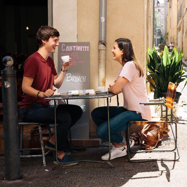 Simon und seine Freundin sitzen in einem Café in Marseille