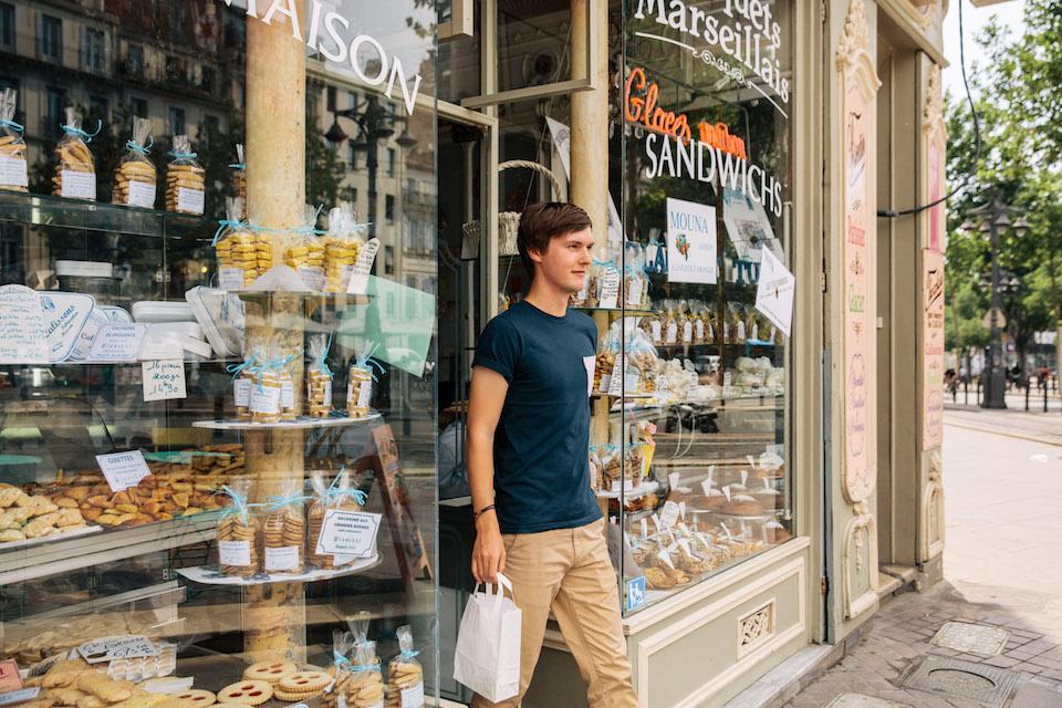 Simon verlässt mit seinen Einkäufen eine Boulangerie in Marseille.