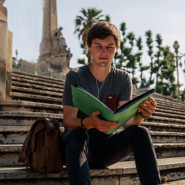 Simon sitzt lesend auf einer Treppe in Marseille.