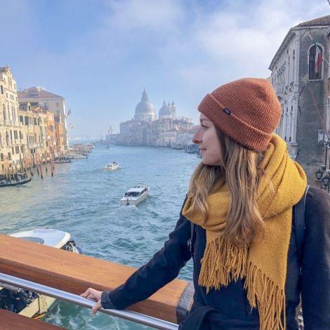 Carina steht auf einer Brücke in Venedig. Hinter ihr sind der Kanal und alte Gebäude zu sehen.
