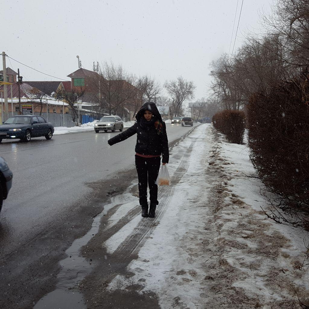 Eine Frau wartet mit zur Seite weggestrecktem Arm am Straßenrand, es ist Winter.