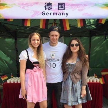 Mit Dirndl und Deutschlandtrickot vor dem Deutschen Stand
