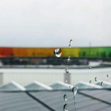 Man sieht regentropfen auf einer Glasscheibe, im Hintergrund sieht man dieRegenbogen-Aussichtsplattform des Aros Museums in Aarhus.