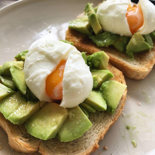 Man sieht zwei Toast mit Avocados und weichgekochten Eiern drauf
