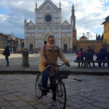 Korrespondentin Julia auf Fahrrad auf der Piazza vor Santa Croce.