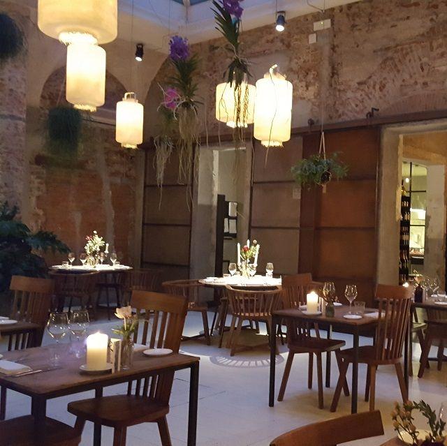 Kleine Tischgruppe unter Lampions und Orchideen die von der Decke hängen.