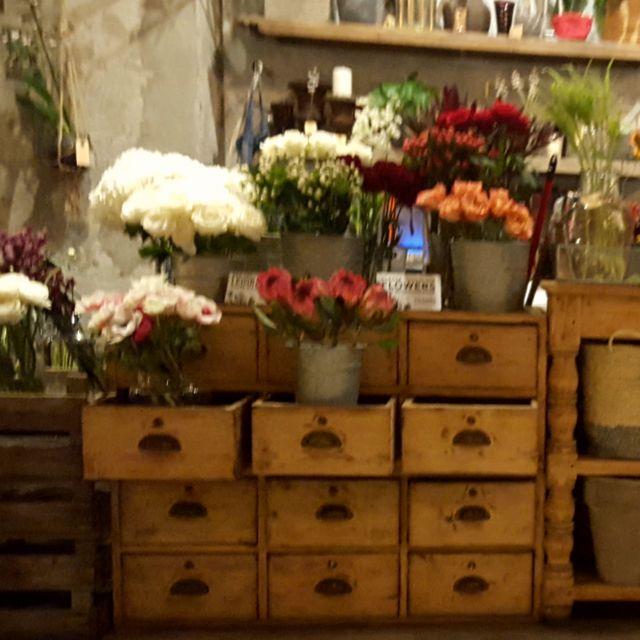 Blumen auf einem hölzernen Verkaufstisch mit Schubladen, aus denen ebenfalls Blumenkübel herausragen.