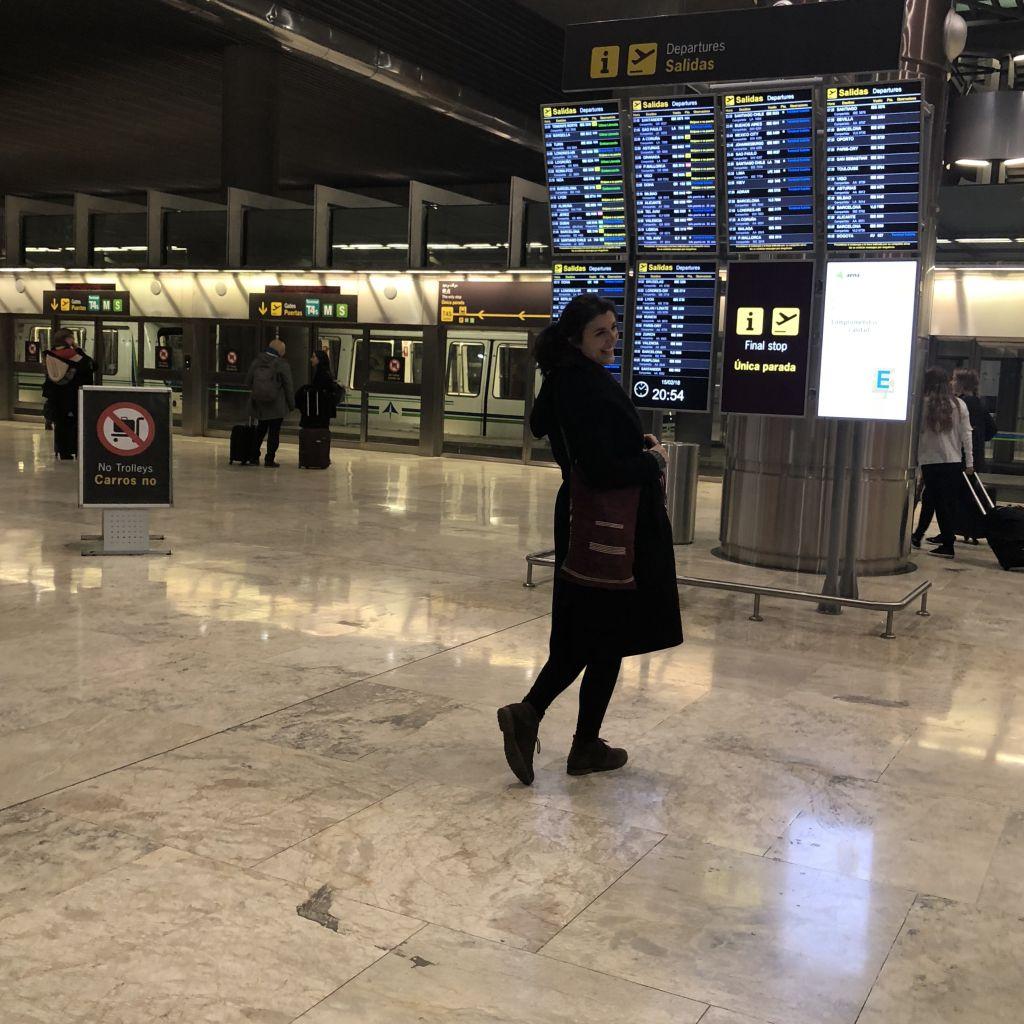 Im Hintergrund sieht man die U-Bahn im Flughafen Madrid sowie die Flug-Anzeigetafel. In der Mitte stehe ich lächelnd mit meinem Wintermantel.