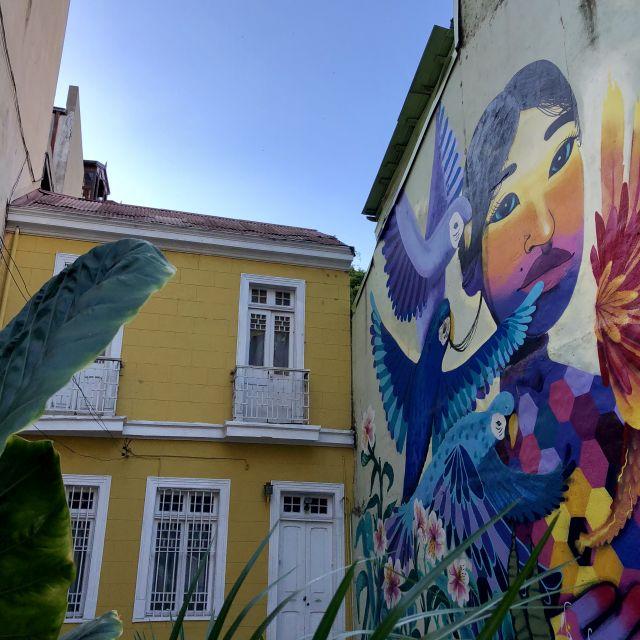 Gelbes Haus und angrenzende Wand bemalt mit einer asiatischen Frau und bunten Vögeln