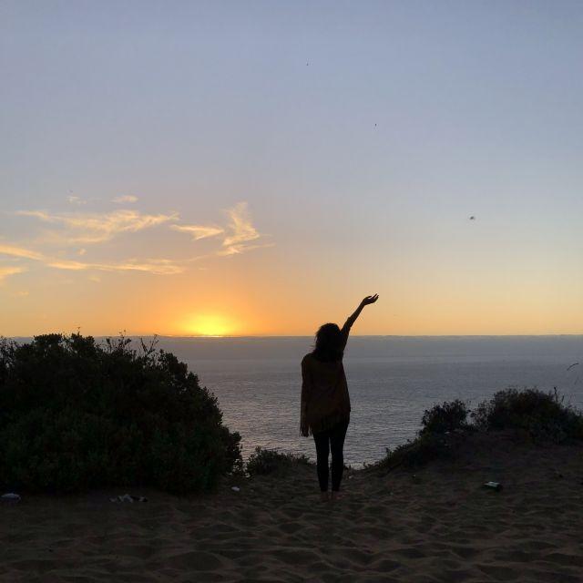 Ich stehe mit Blick zum Meer im Sonnenuntergang