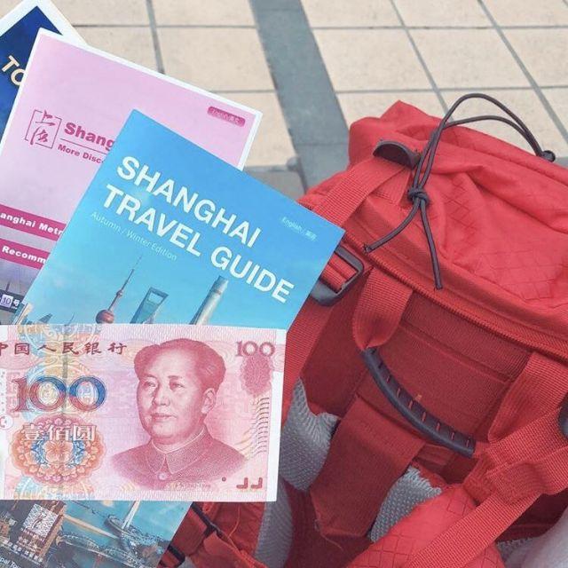 Das Bild zeigt einen roten Rucksack, einen Reiseführer für Shanghai und eine Banknote in chinesischer Währung.