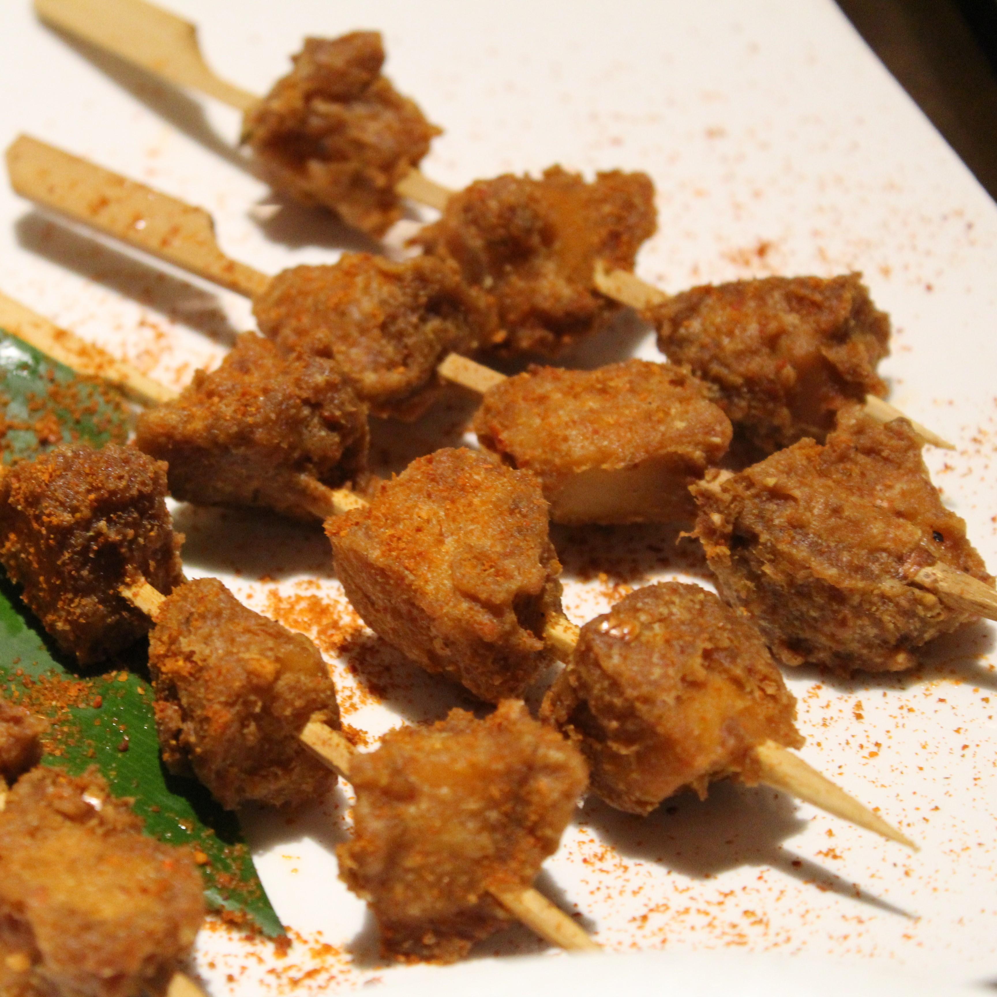 Das Bild zeigt einen weißen Porzellanteller mit Schaschlikspießen, welche Seitan-Würfel enthalten.