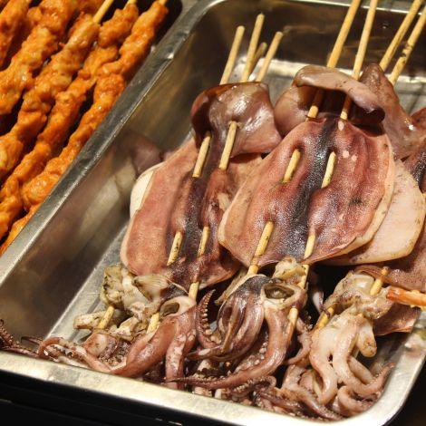 Das Bild zeigt aufgespießte, gebratene Tintenfische an einem Street-Food-Stand.
