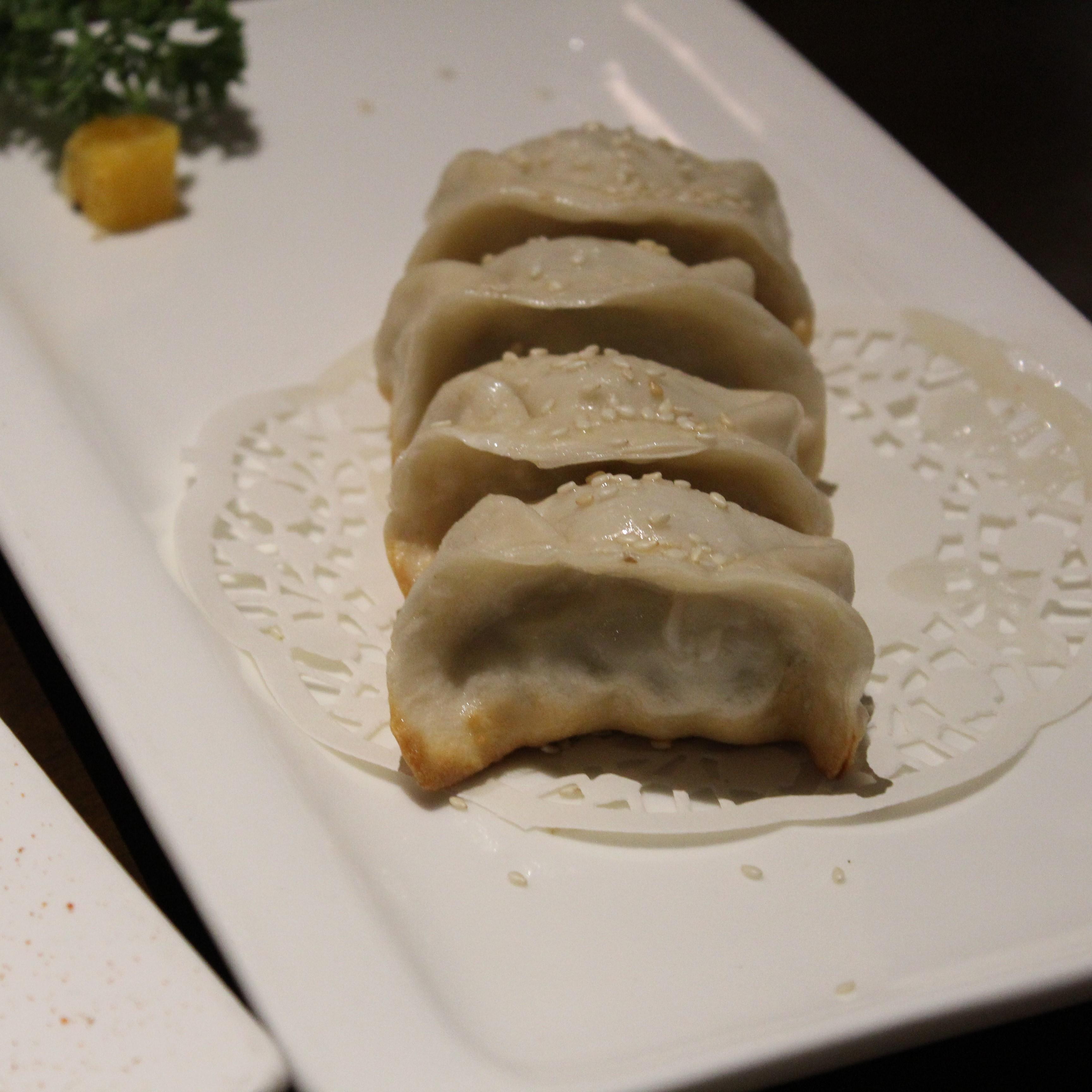 Das Bild zeigt einen weißen Porzellanteller mit gefüllten und gebratenen Teigtaschen, sogenannten Dumplings.