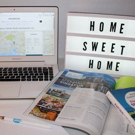 """Das Bild zeigt einen Schreibtisch, auf dem ein Laptop mit der geöffneten Seite von Daimler South East Asia Pte. Ltd steht. Daneben liegt ein Reiseführer von Singapur. Komplettiert wird das Bild durch eine Leuttafel mit der Schrift """"Home Sweet Home""""."""