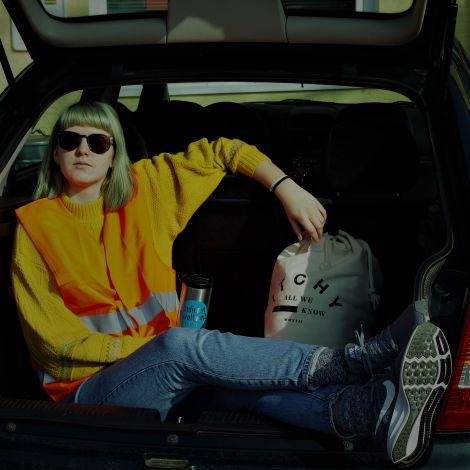 Junge Frau sitzt bekleidet mit einer Warnweste im Kofferraum ihres Wagens und blickt nachdenklich in die Sonne