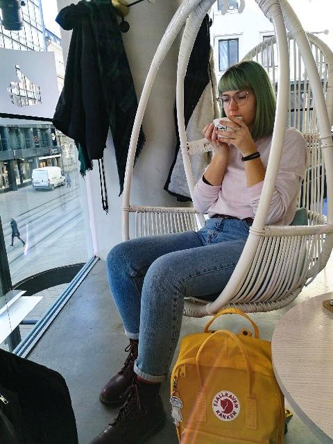 Junge Frau sitzt mit einer Tasse in einem Korbstuhl, der von der Decke hängt. Im Hintergund sieht man durch eine Scheibe die Straße.
