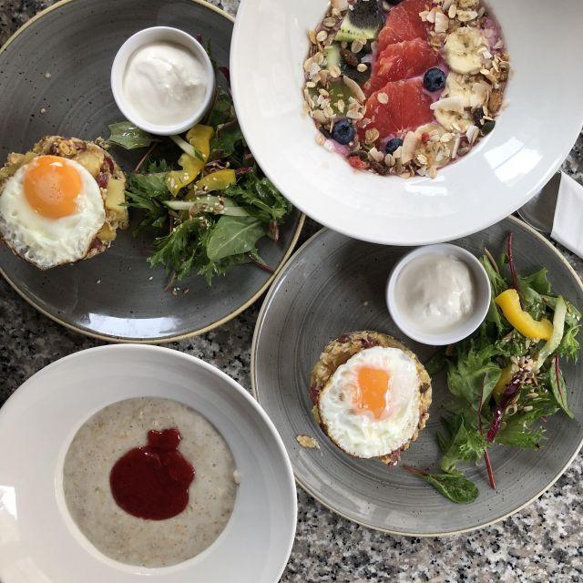 Vier Teller mit Porridge, Joghurt mit Müsli und Spiegelei mit Kartoffeln.