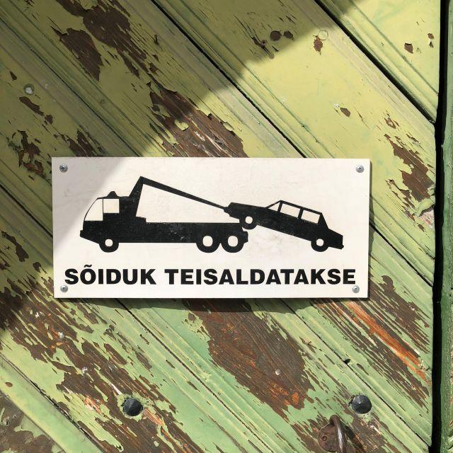 Ein Schild warnt auf estnisch vor dem abschleppen widerrechtlich geparkter Fahrzeuge.
