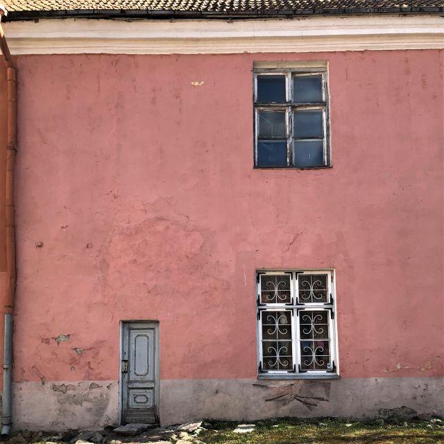 Rosa Haus mit blättriger Fassade, zwei Fenstern und Tür