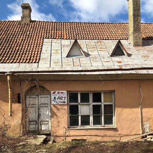 verfallenes oranges Haus mit einem Schild, das auf eine wohl nicht mehr existente Kunstgalerie hinweist.