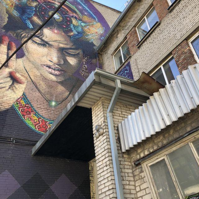Graffiti einer Frau and er Wand einer alten Fabrikhalle