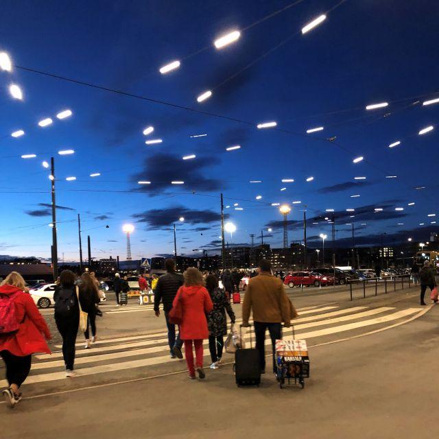 Menschen überqueren einen Zebrastreifen am Länsisatama in Helsinki
