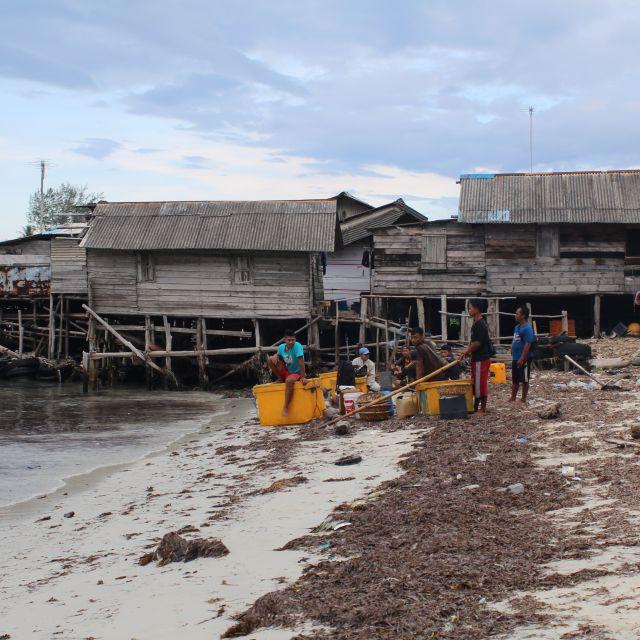 Das Bild zeigt eine Fischerhütte auf Pfählen. Im Vordergrund sitzen Fischer in einem Kreis.