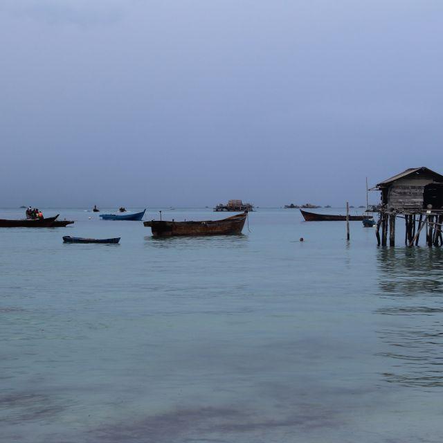 Das Bild zeigt einen wolkenverhangenen Himmel und Fischerboote sowie eine -Hütte auf Pfählen.