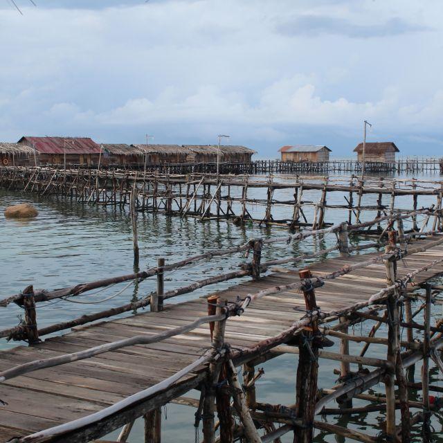 Das Bild zeigt einen Holzsteg, der zu einer Reihe an Holzhütten, die auf Pfählen auf dem Wasser stehen, führt.