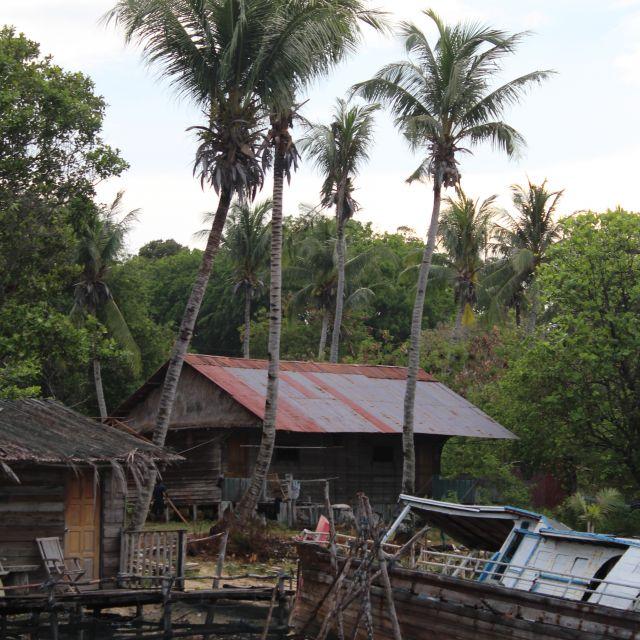 Das Bild zeigt ein am Strand liegendes, baufälliges Boot, im Hintergrund sind Palmen sowie ein Haus zu sehen.