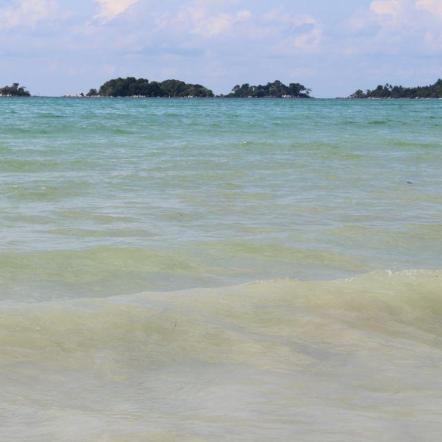 Das Bild zeigt das türkisblaue Meer. im Hintergrund sind einige kleine Inseln zu sehen.