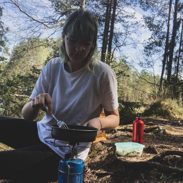 Frau grillt auf einem Gaskocher im Wald