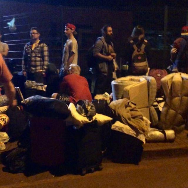 Menschen mit Matratzen und Koffern