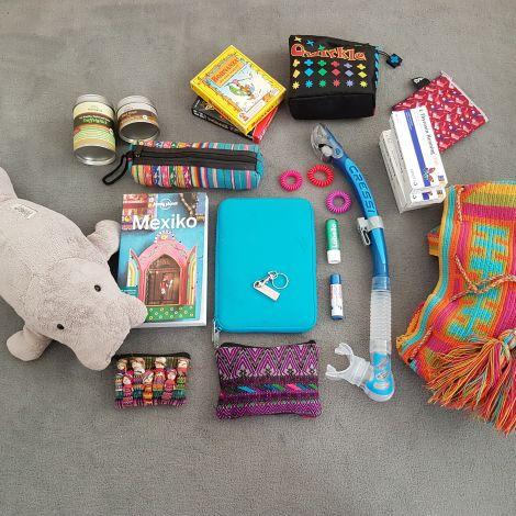 Reisegepäck bestehend aus einem Beutel, Reiseführer, Tablet, Kartenspielen, Kuscheltier, Schnorchel, Federtasche, Gewürzen, Medikamenten, Portemonnaie, USB stick und Kosmetika