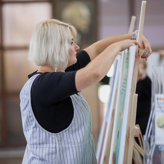 Beim Aufbau einer Staffelei bei einer Kunstausstellung