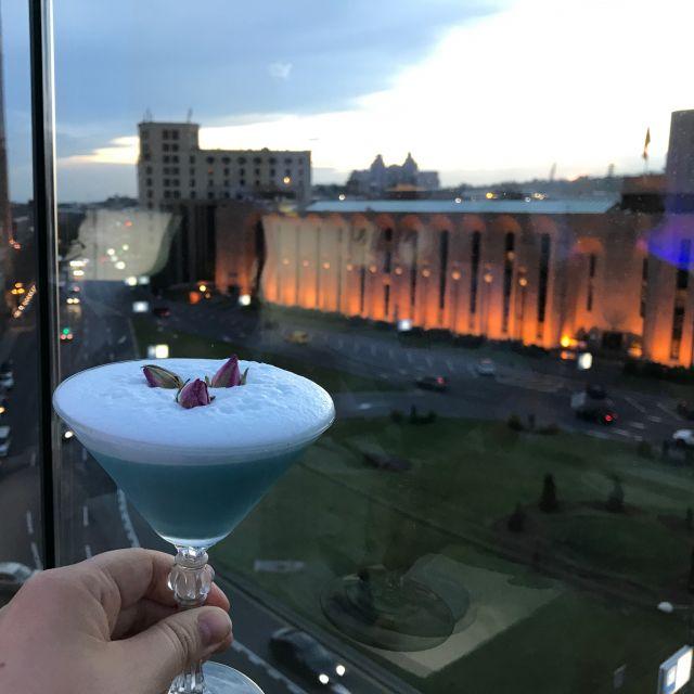 Ein Cocktail vor einem beleuchteten Gebäude