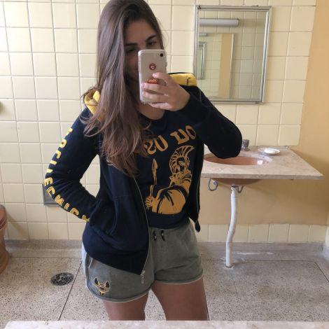 Mädchen fotografiert sich im Spiegel mit Unikleidung