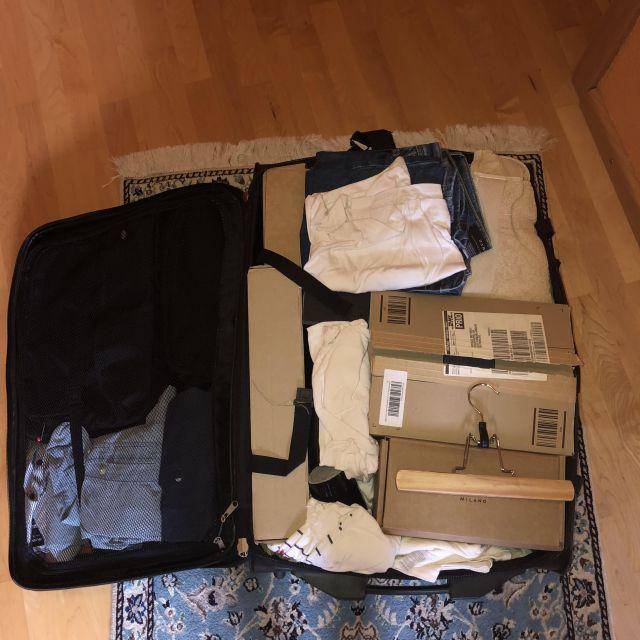 Auf dem Boden steht ein Koffer voller Klamotten.