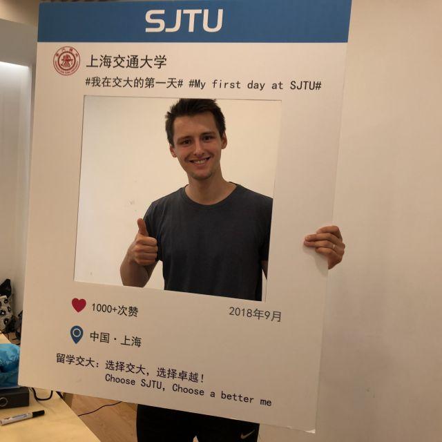 Nicholas hält ein Schild der Shanghai Jiao Tong University in der Hand.