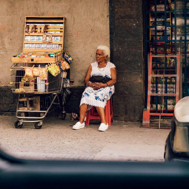 Eine alte Frau neben einem Straßenstand in Medellín.